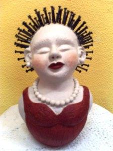 Busto de barro com cabeça de pregos
